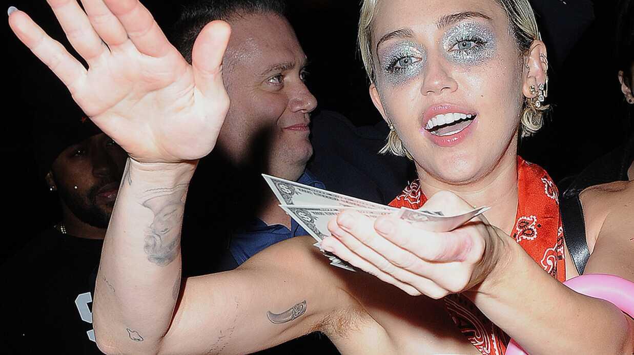 PHOTOS Miley Cyrus distribue aux photographes des billets à son effigie